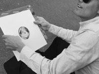 Bilde av mann med solbriller som holder en vinylplate