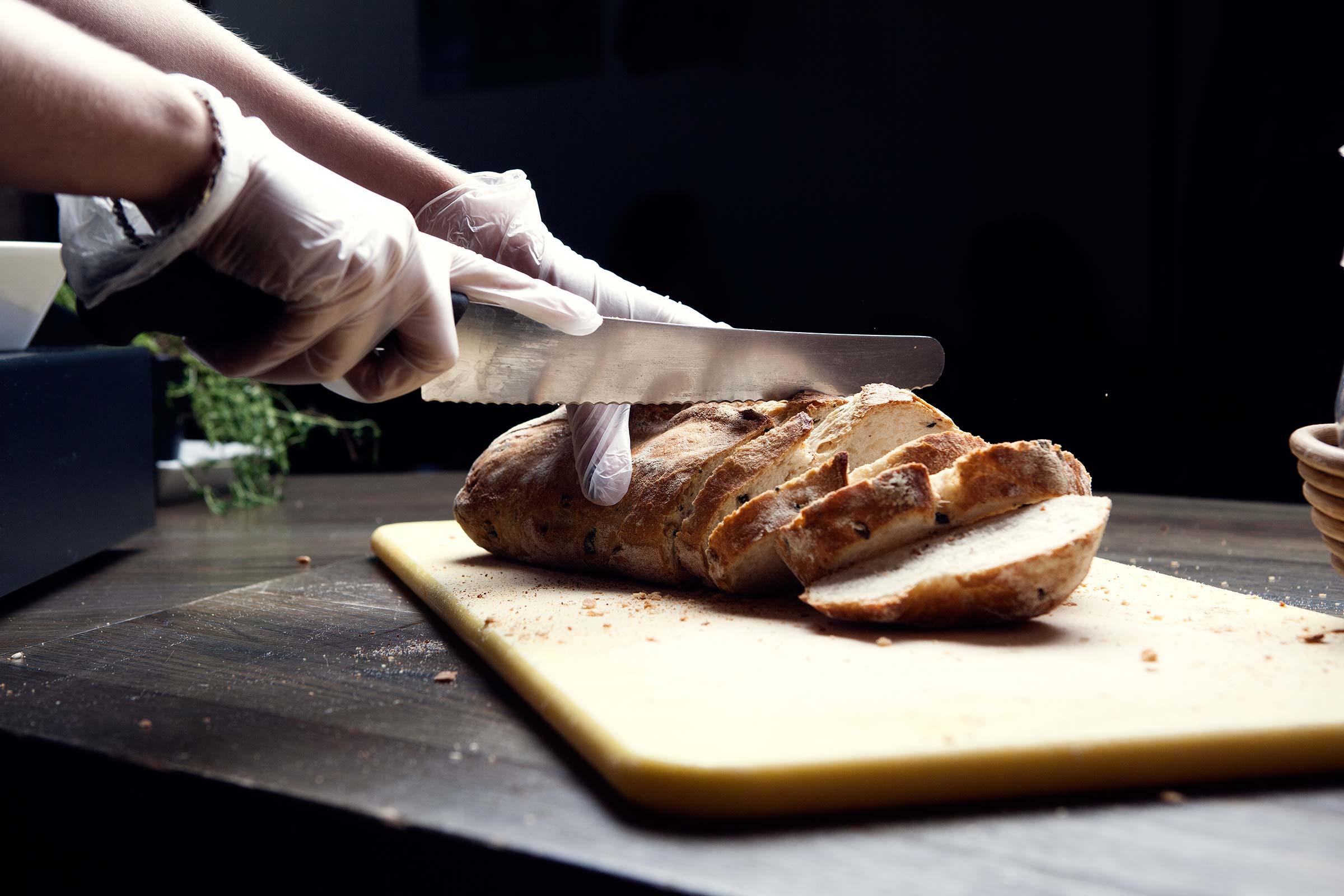 Bilde av noen som skjærer opp brød på en fjøl