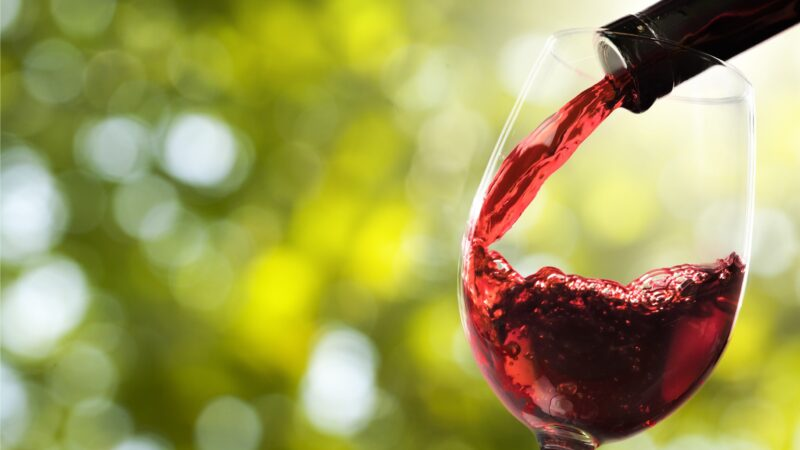 Red wine and glass on background